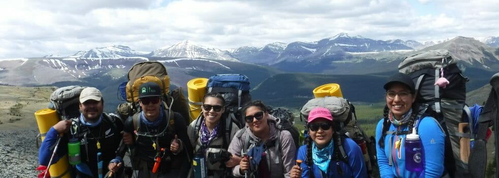 hikers smile at camera atop mountain
