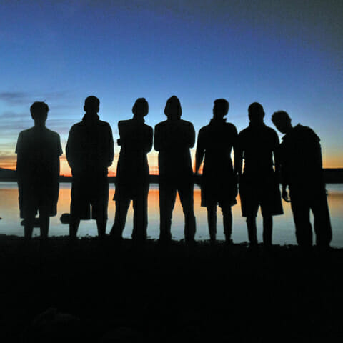 Silhouette-of-students-standing-on-shore-with-sunset-in-background