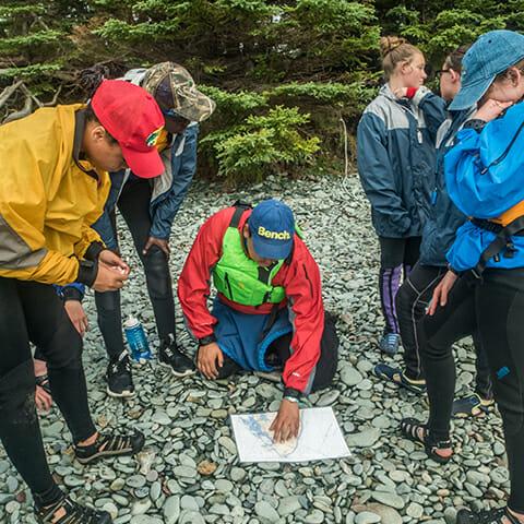 Six people gathered around a map