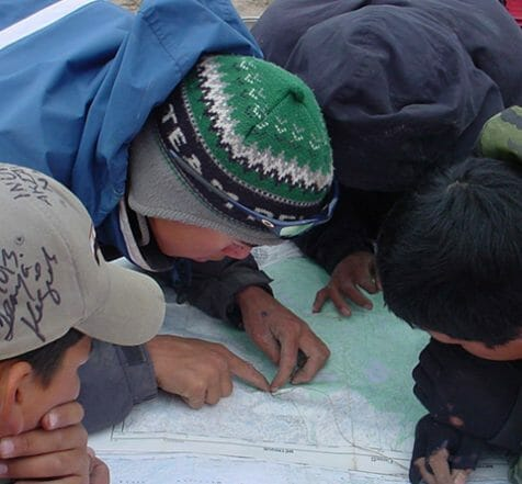 group-of-indigenous-boys-reading-map