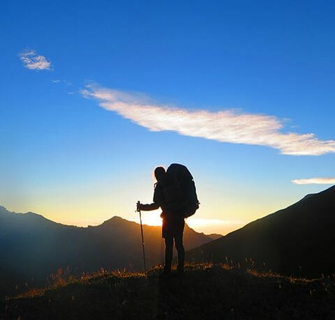 Silhouetted hiker watching sunset