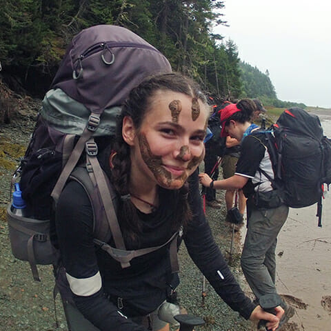 smiling_backpacker_with_mud_on_her_face