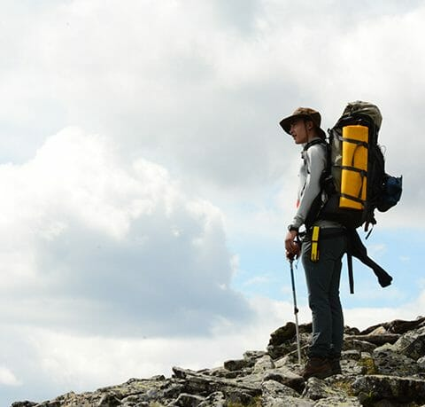 solo_hiker_standing_on_rocks_looking_into_the_distance