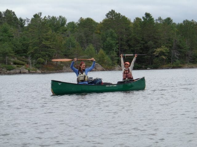 2 canoers holding paddles over head in a canoe