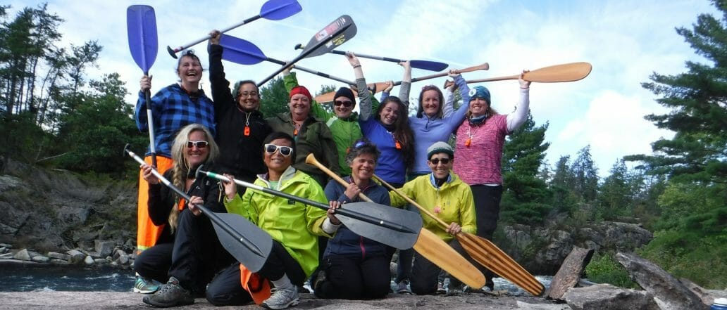 Group of people holding canoe and kayak paddles over head