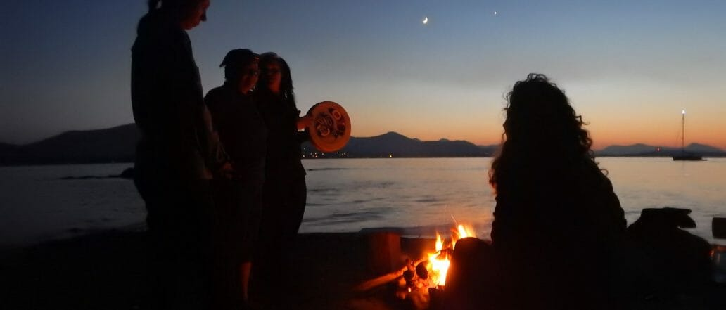 Group of people around a fire at sunset