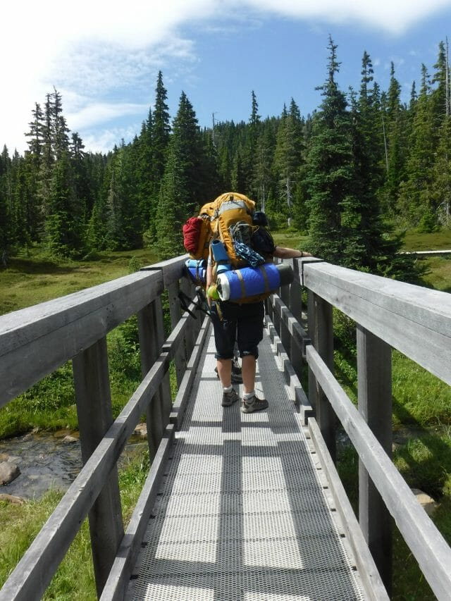 Person crossing wooden bridge with backpack on