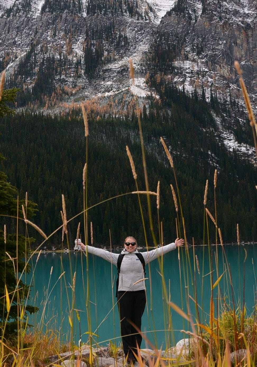 Girl Arms stretched wide by blue lake mountains hiking