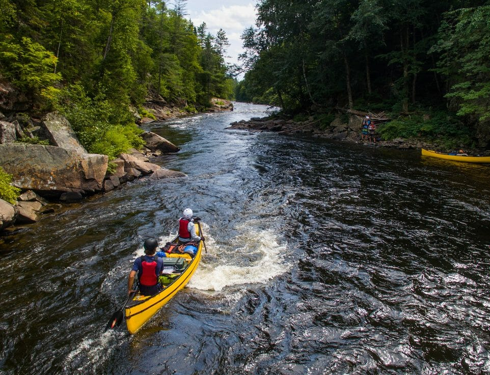 Two yellow canoes being paddles down river through rapids. Trees and rocks on shore.