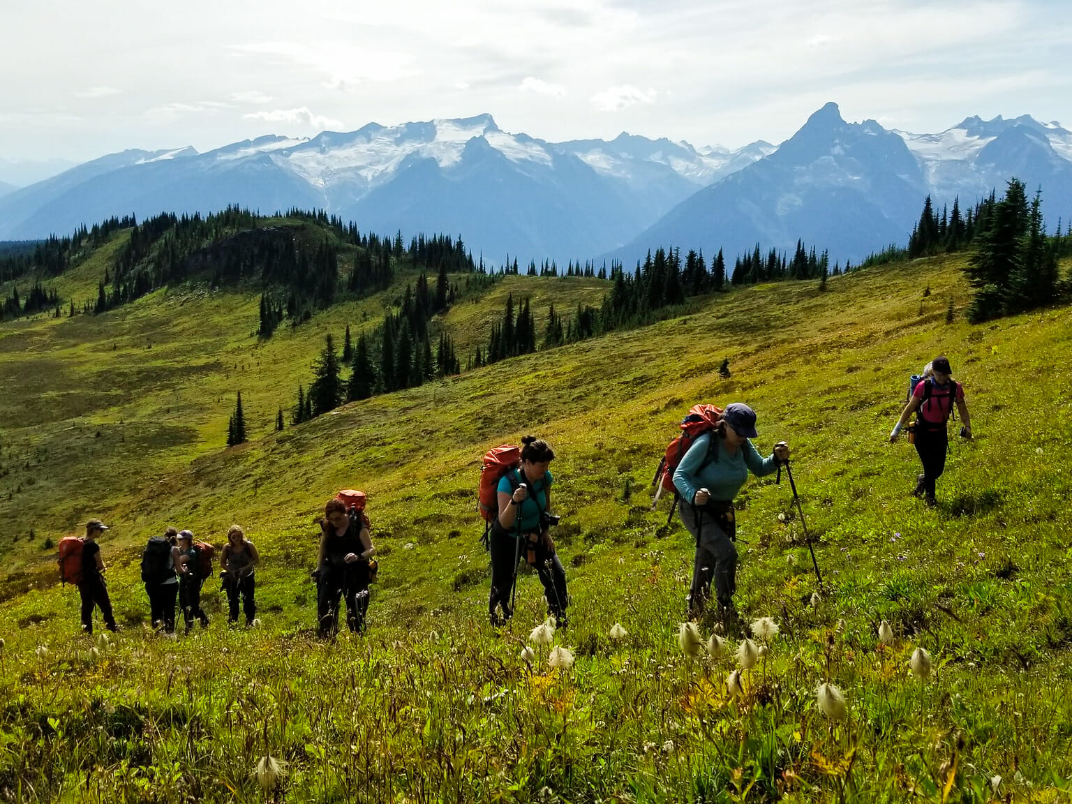 Line of people hiking up a grass covered slope