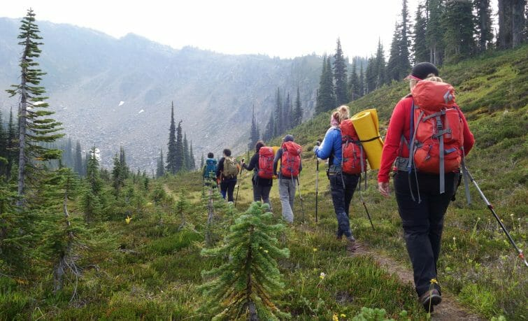 hikers walk into valley
