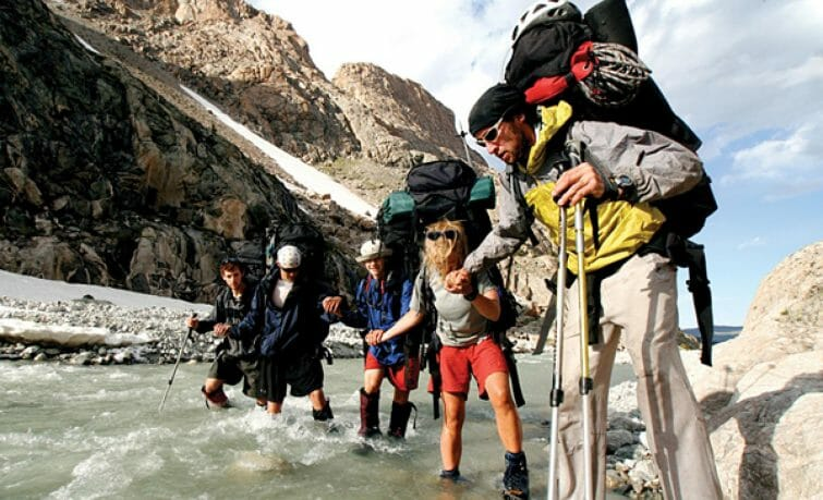 group of hikers crossing a river