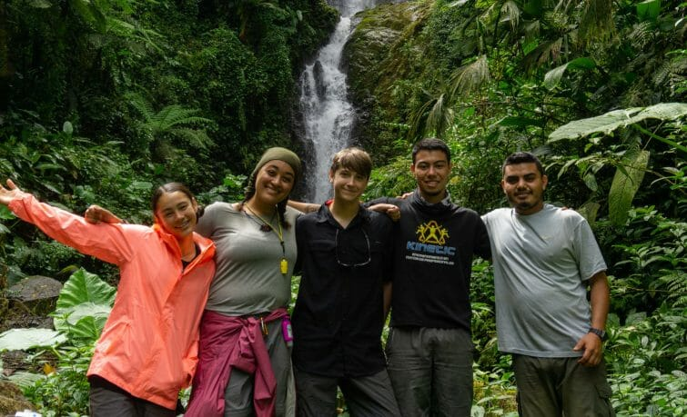 hikers smile in front of waterfall