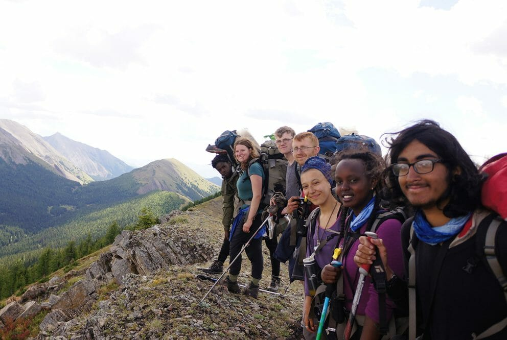 Group of people smiling on top of a mountain