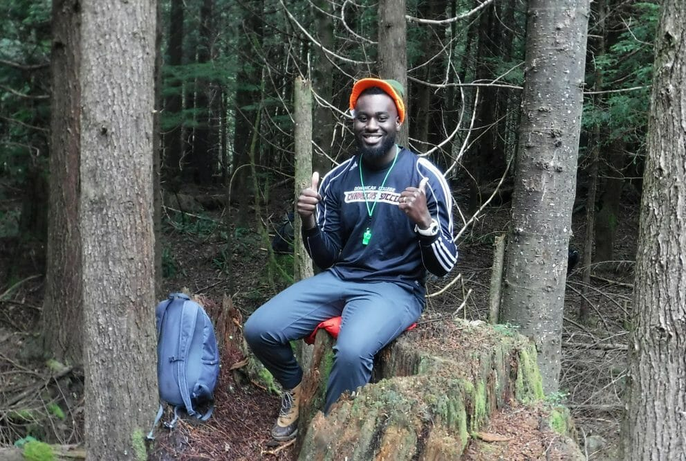 man sitting on treestump with thumbs up