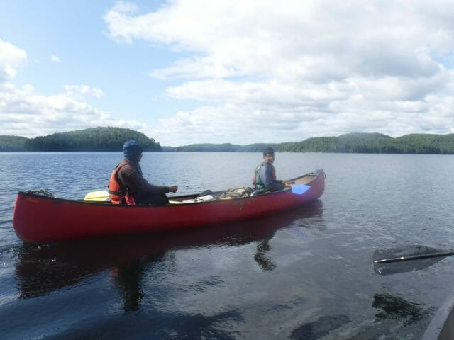 two people sitting in canoe on lake