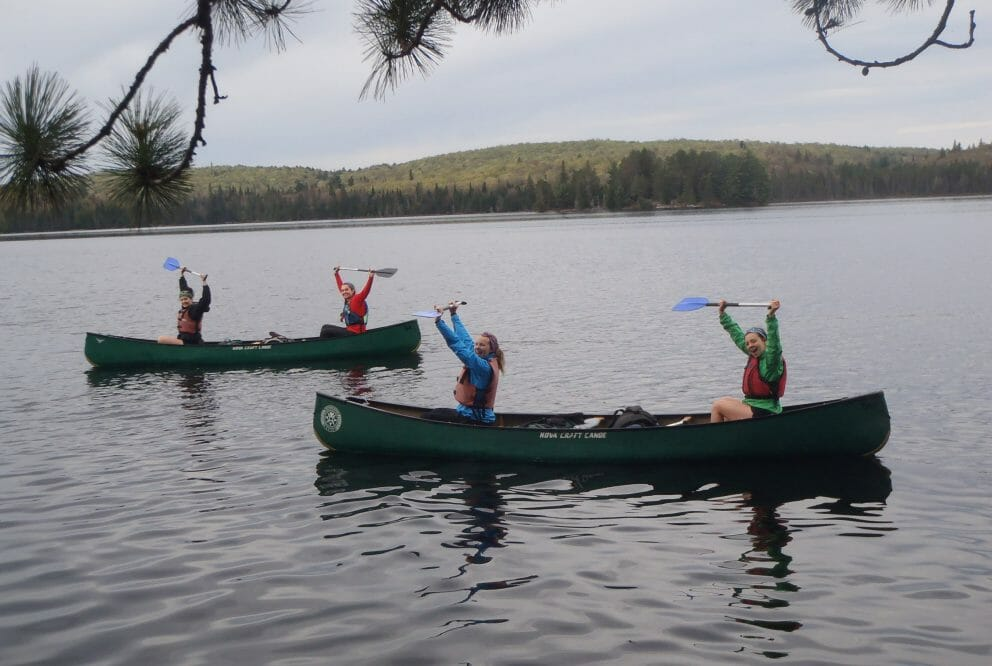 people cheering in canoes on lake