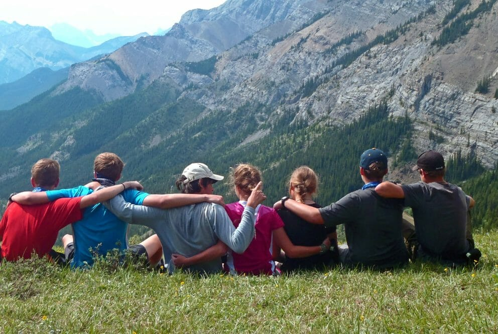 group of people sitting in grass looking over valley