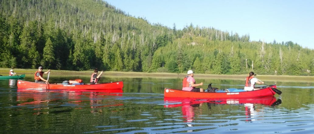 Three red canoes on lake in front of mountain
