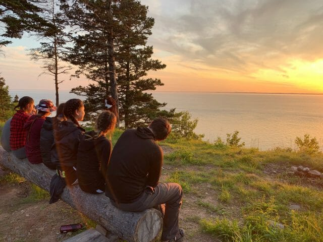 group of seven students watching sunset over ocean