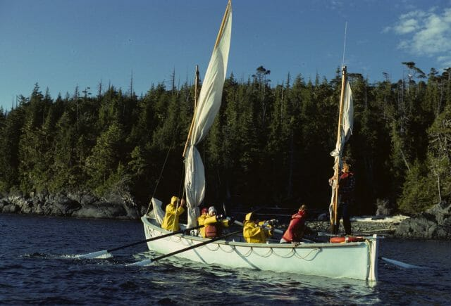 Large row boat with sails in lake in front of forest
