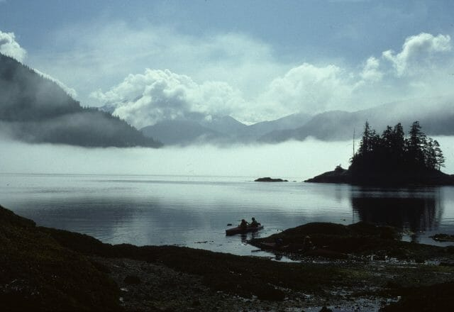 foggy mountains over lake with kayakers