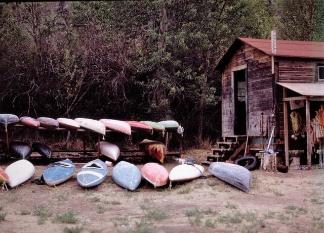 wood cabin with kayaks outside