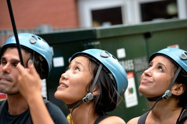 Three climbers wearing helmets looking up