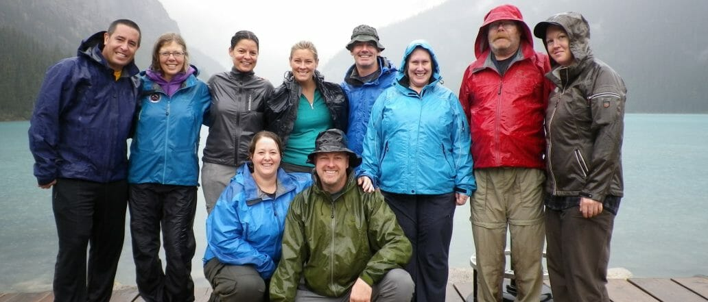 Group posing for photo on a doc in rain jackets