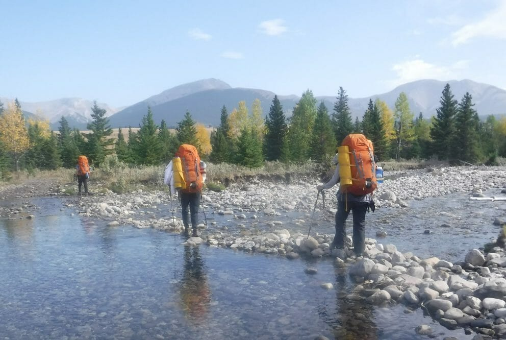 Three people crossing rocky stream with backpacks, mountains and trees in the distance