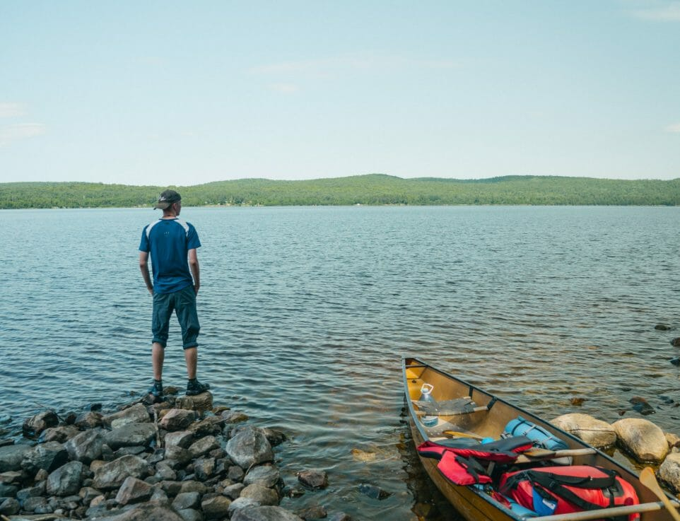 Person standing on rocks looking out across a lake. Canoe is beside them on shore