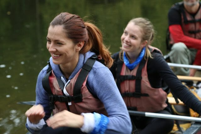 women smiling in canoe