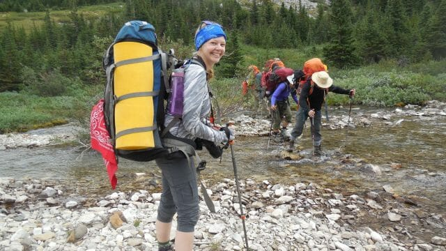 Backpacker smiling about to cross a river