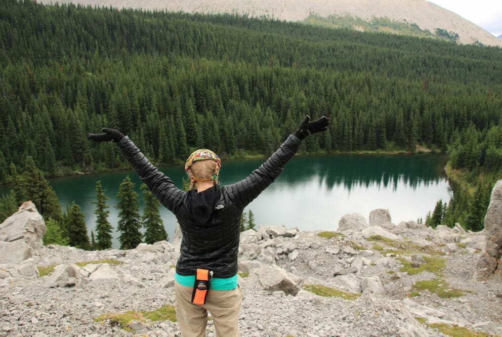 Person with arms up overlooking lake