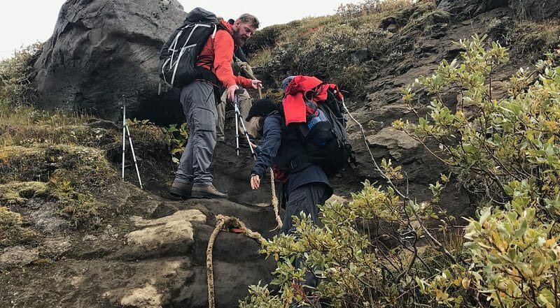 hikers ascending mountain in iceland