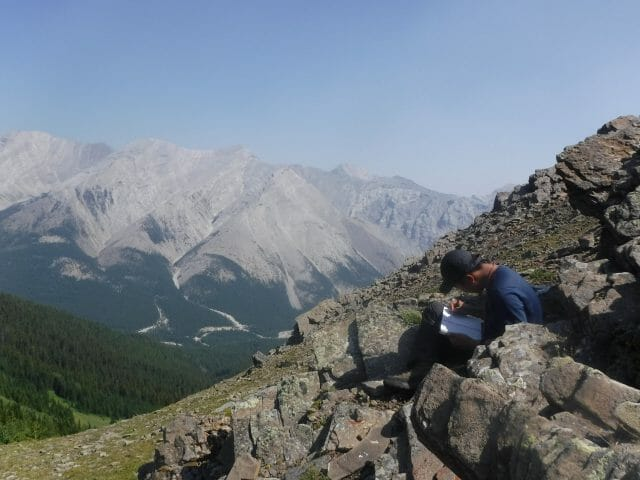 Person writing in journal on the side of a mountain