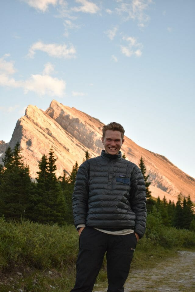 Person smiling in front of a mountain