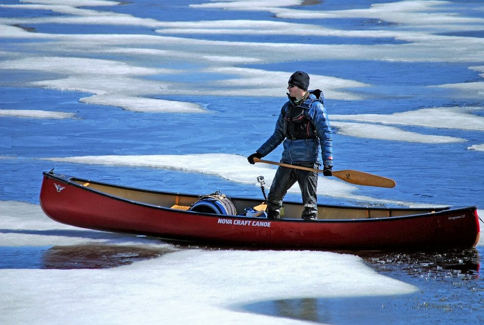 Man standing while canoeing through ice