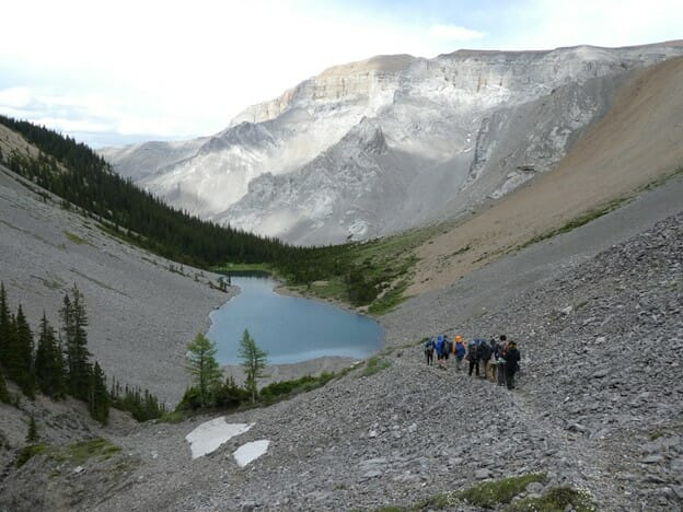 Group in the distance walking along a mountain path with a lake at the bottom