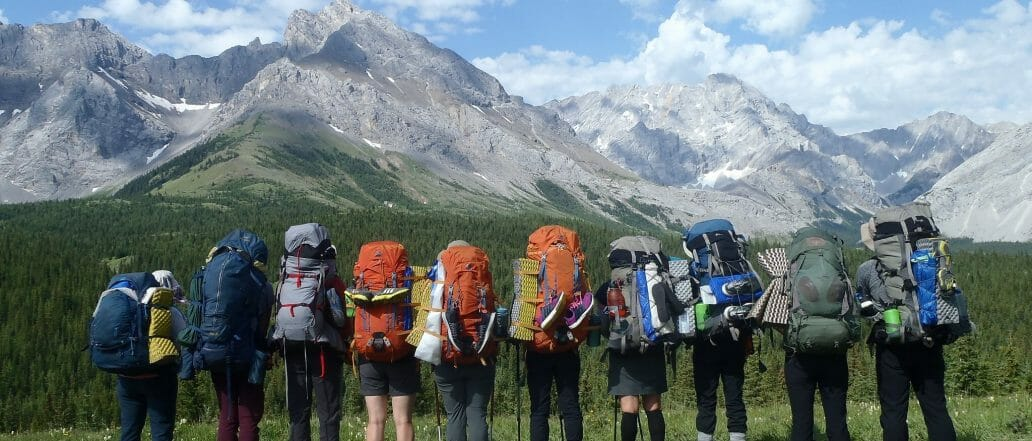 Ten people with hiking backpacks looking out at Mountains