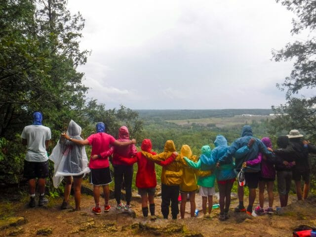 Group of people linked arms in rainbow-coloured rain jackets