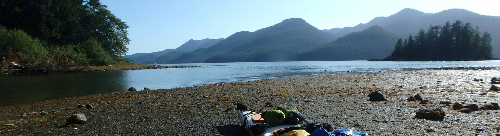 Kayak on a beach. Still water and tree covered hills in the distance.