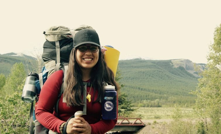 Person smiling with water bottle, mountain in background