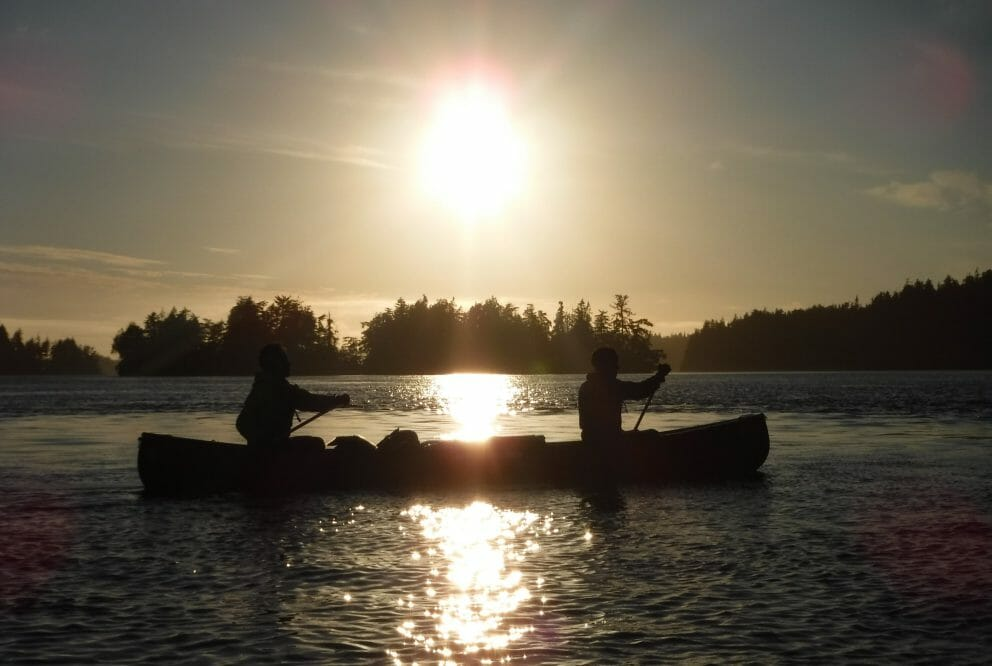Silouette of two people in a canoe on a lake