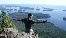person sitting on rock overlooking ocean