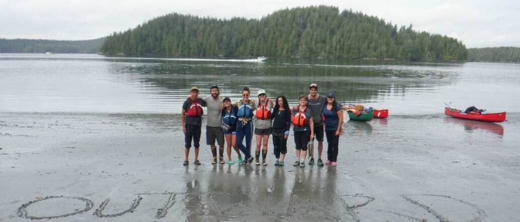 Group posing in front of lake with Outward Bound 19 written in the sand
