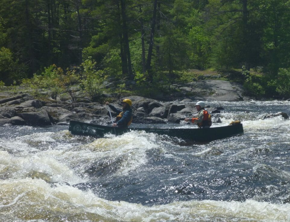 Two people canoeing in white water rapids