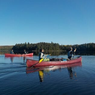 Two red canoes in still water with 2 paddlers in each