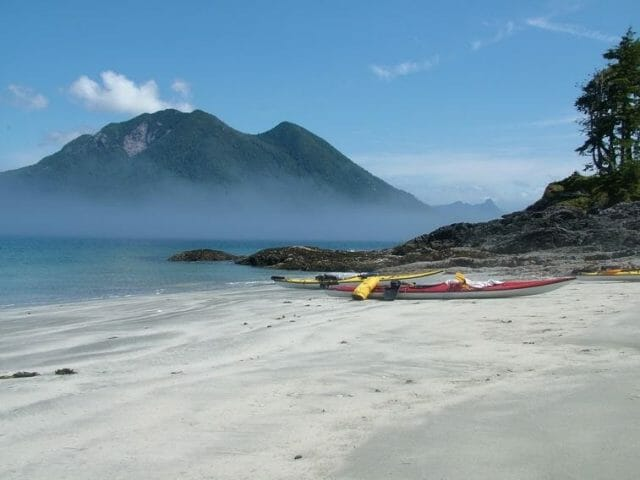 Kayaks on a sandy beach. Fog covered mountains in the distance