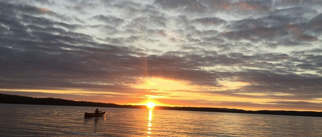 A canoer on a lake at sunset. Cloudy sky overhead and waves lapping on shore